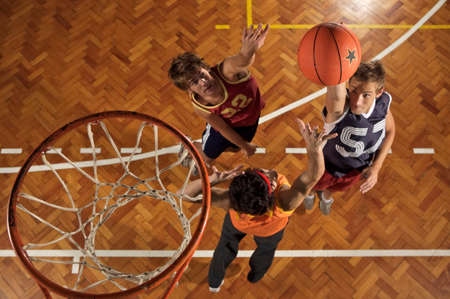 young men: High angle view of three young men playing basketball