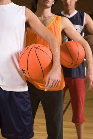 basketballs: Three young men standing in a court and holding basketballs LANG_EVOIMAGES