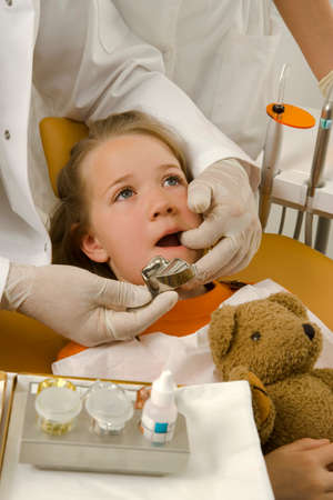examining: Dentist examining a girls teeth