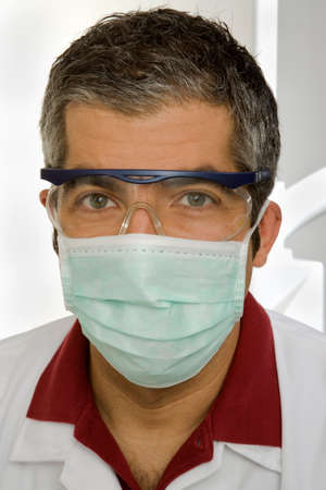 protective eyewear: Portrait of a male dentist wearing a surgical mask and protective eyewear