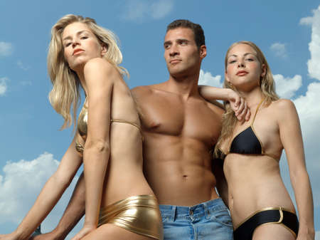 playboy: Low angle view of a young man standing with two young women beside him