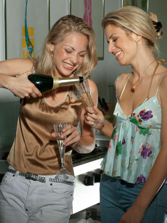 female bonding: Two young women with champagne LANG_EVOIMAGES