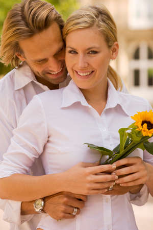 rolledup sleeves: Portrait of a young man embracing a young woman holding a flower and smiling