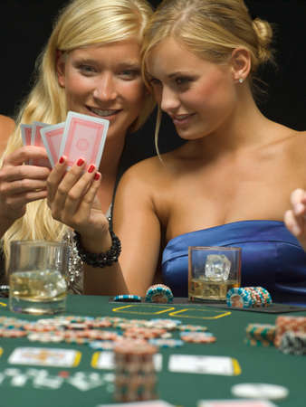 poker game: Women looking at playing cards at poker game LANG_EVOIMAGES