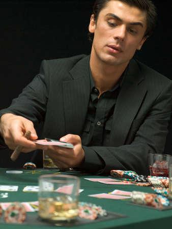 european ethnicity: Man dealing playing cards at poker game