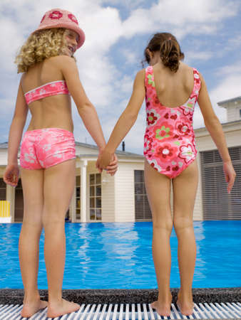 girls holding hands: Las ni�as de la mano cerca de la piscina LANG_EVOIMAGES