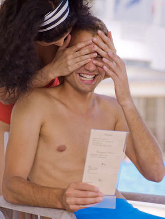 bare waist: Woman covering mans eyes near pool