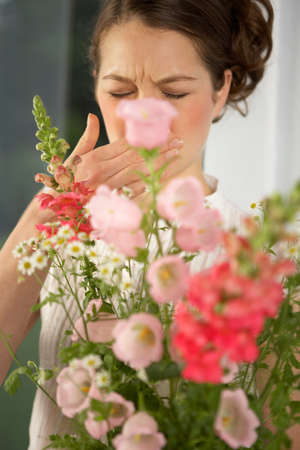 mid adult woman: Mid adult woman sneezing behind a bouquet of flowers LANG_EVOIMAGES