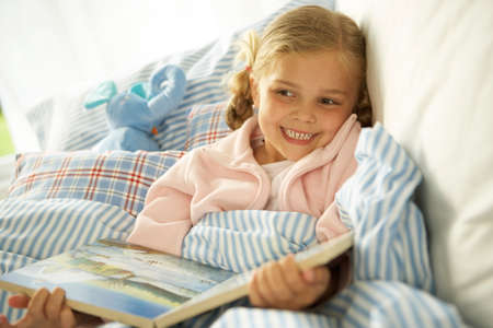 picture book: Close-up of a girl holding a picture book on the bed and smiling