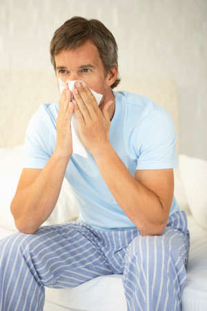 striped pajamas: Mid adult man suffering from cold LANG_EVOIMAGES