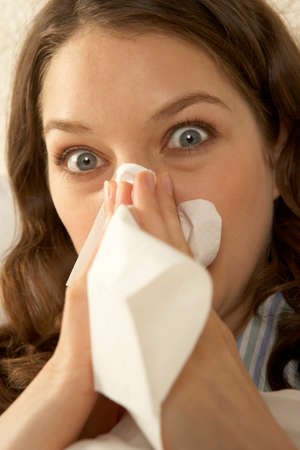 sneezing: Portrait of a mid adult woman sneezing