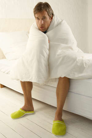 duvet: Portrait of a mid adult man wrapped in a duvet and sitting on the bed