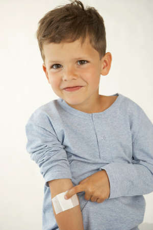 adhesive bandage: Portrait of a boy showing an adhesive bandage on his hand LANG_EVOIMAGES