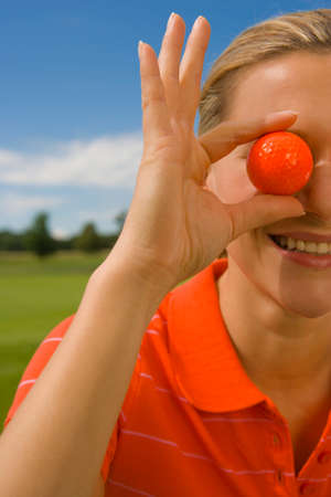 eye ball: Close-up of a mid adult woman holding a golf ball in front of her eye and smiling