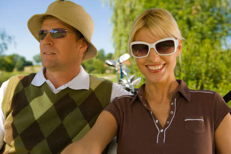 mid adult couple: Close-up of a mid adult couple sitting in a golf cart and smiling