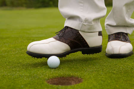 low section view: Low section view of a man putting a golf ball into a hole with a foot LANG_EVOIMAGES