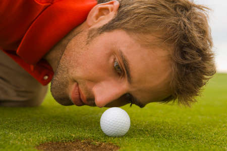 judging: Close-up di un uomo adulto a met� giudicare una pallina da golf su un campo da golf