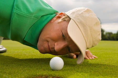 judging: Close-up of a mid adult man judging a golf ball on a golf course