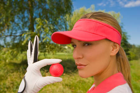one mid adult woman only: Portrait of a mid adult woman holding a golf ball LANG_EVOIMAGES