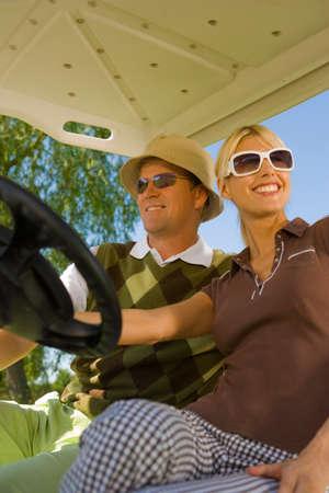 mid adult couple: Pareja de mediana edad sentado en un carrito de golf y sonriendo
