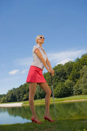 sandal tree: Side profile of a mid adult woman standing on a golf course and holding a golf club
