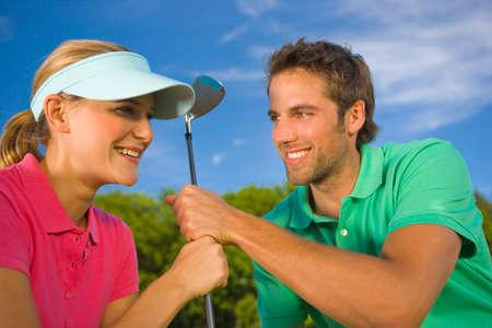 mid adult couple: Primer plano de una pareja de mediana edad la celebraci�n de un club de golf y sonriendo