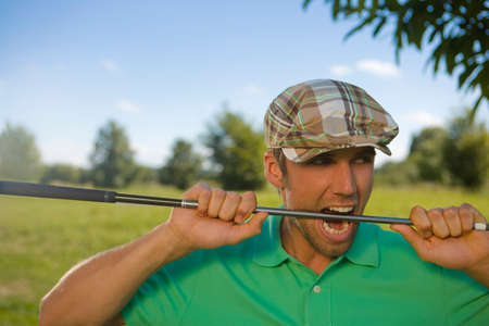 only one mid adult man: Close-up of a mid adult man biting a golf club