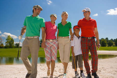 mid adult couples: Two mid adult couples with a boy walking on the sand trap on a golf course LANG_EVOIMAGES