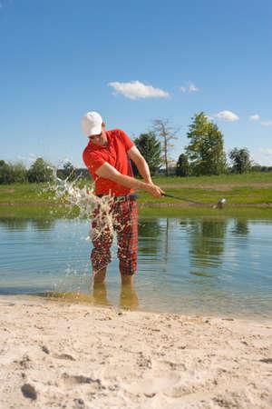 waterhole: Mediados de hombre adulto golpeando una pelota de golf en el pozo de agua en un campo de golf