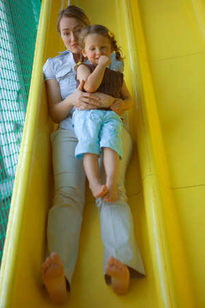 hair part: Portrait of a mid adult woman with a girl sliding on a slide