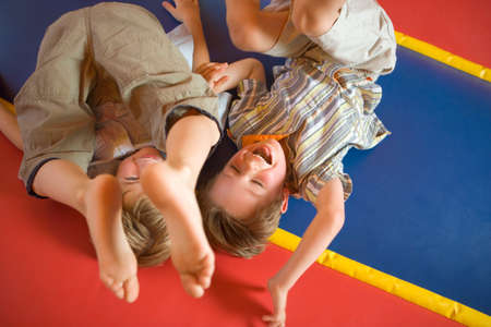 indoors: High angle view of two boys playing on an inflatable bouncy castle