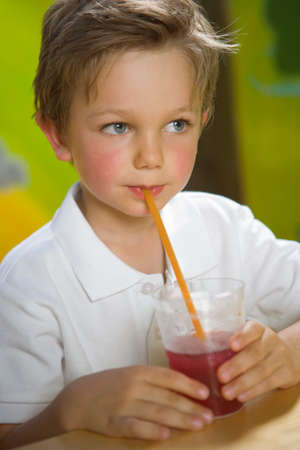 drinking straw: Close-up di un frullato ragazzo bere con una cannuccia