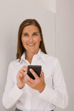 datos personales: Retrato de una mujer de mediana edad utilizando un asistente de datos personales y sonriente