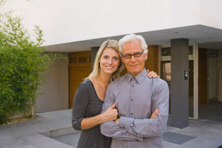 arm around: Portrait of a mid adult woman with arm around her father and smiling