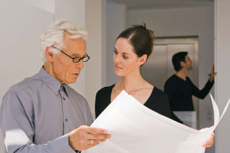 receding hairline: Businessman and a businesswoman discussing a blueprint in an office