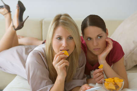 earnest: Two women eating crisps LANG_EVOIMAGES