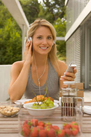 tanktop: Woman listening to MP3 player LANG_EVOIMAGES