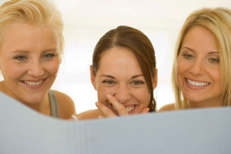 off shoulder: Close-up of three women reading LANG_EVOIMAGES