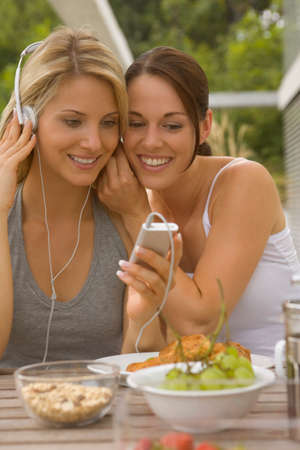 two persons only: Two women listening to MP3 player