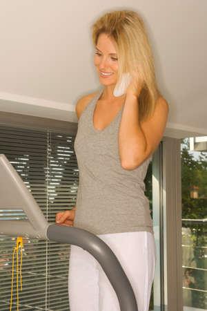 phoning: Woman on treadmill phoning