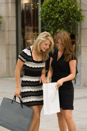 retail therapy: Young women looking in shopping bag LANG_EVOIMAGES