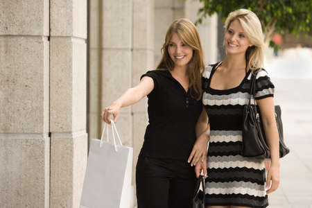 retail therapy: Young women shopping together and woman pointing