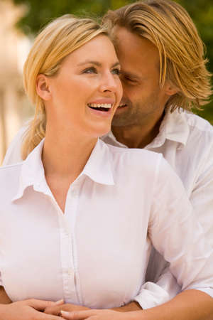 woman from behind: Close-up of a young man embracing a young woman from behind