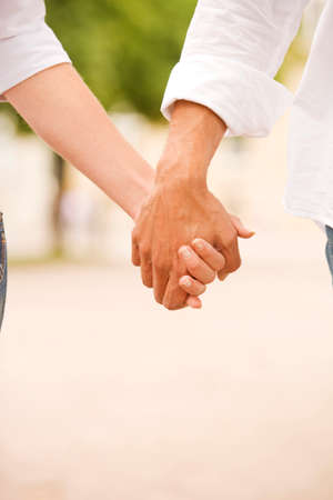 rolledup sleeves: Close-up of a man and a woman holding each others hands