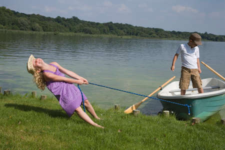 tugging: Young girl pulling boat with boy in it to shore