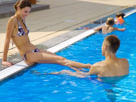 tugging: Man tugging womans leg at pool