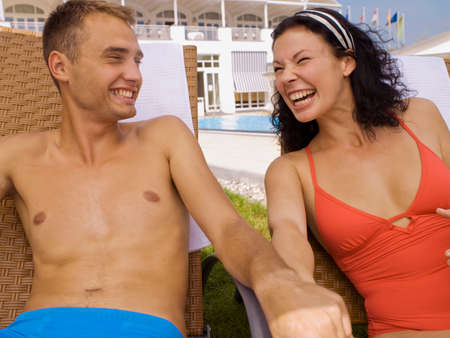 bare waist: Couple laughing near poolside