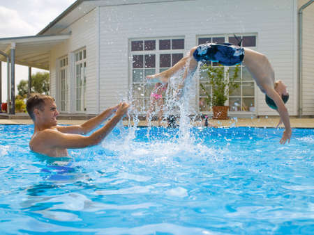 family with two children: Boy doing back flip in pool
