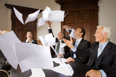 hands lifted up: Happy businesspeople throwing papers in the air