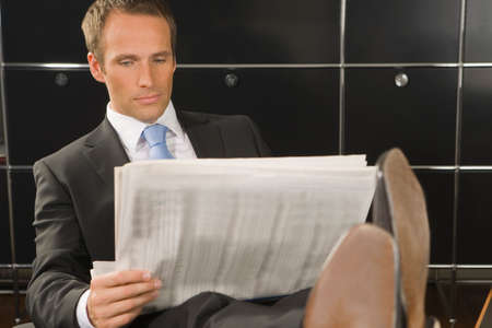financial newspaper: Businessman reading a financial newspaper in an office LANG_EVOIMAGES
